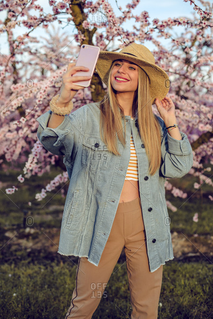 Portrait of a girl taking a selfie with her mobile phone in a pink flower field