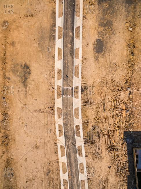 Aerial view of asphalt road crossing construction soil, Australia.