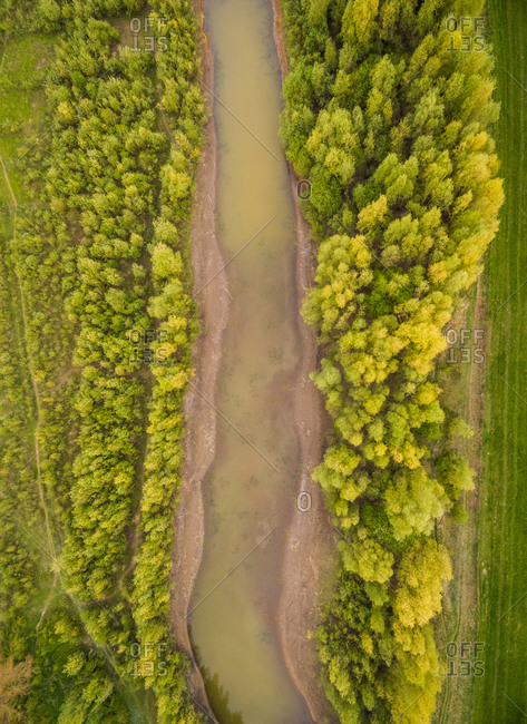 Aerial view of shallow river crossing riparian forest, Netherlands.