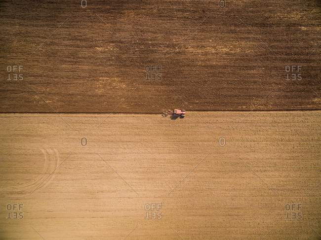 Aerial view of single tractor preparing raw soil for plantation, Netherlands.