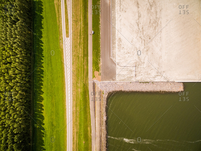 Abstract aerial view of road crossing landscape near dense forest, Netherlands.