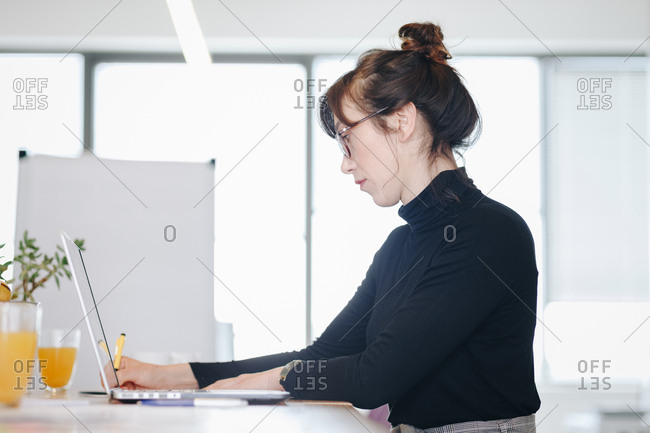 Candid portrait of business woman working and taking notes during a meeting in modern office space