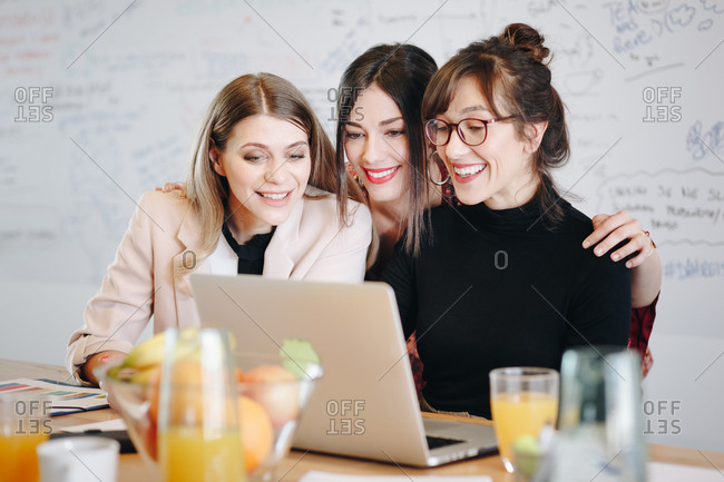 Candid moment, three young beautiful female coworkers talking to boss over video call in the office
