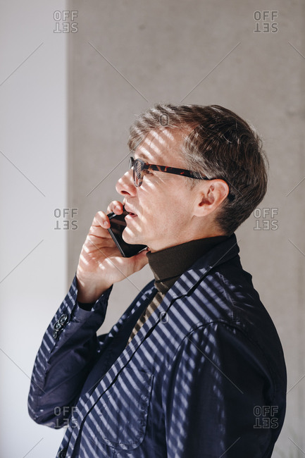 Portrait of  confident businessman standing in new office and talking over phone with partners negotiating a new deal