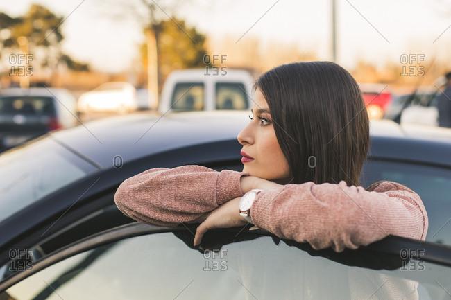 Teenage girl leaning on car door looking at distance