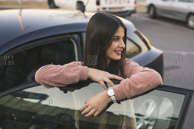 Smiling teenage girl leaning on car door looking at distance