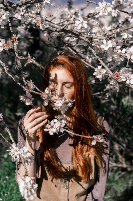 Redheaded woman smelling tree blossoms