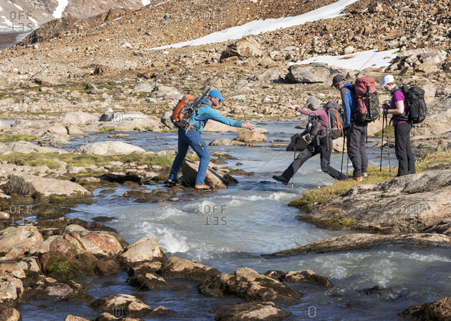 Greenland- Sermersooq- Kulusuk- Schweizerland Alps- group of people crossing brook