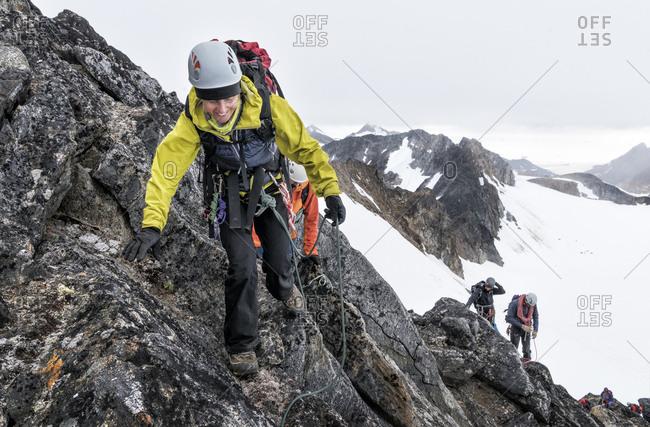 Greenland- Sermersooq- Kulusuk- Schweizerland Alps- mountaineer ascending rocky mountain