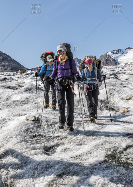 Greenland- Sermersooq- Kulusuk- Schweizerland Alps- three smiling people walking in snowy mountainscape
