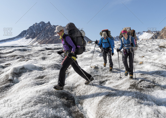 Greenland- Sermersooq- Kulusuk- Schweizerland Alps- three people walking in snowy mountainscape