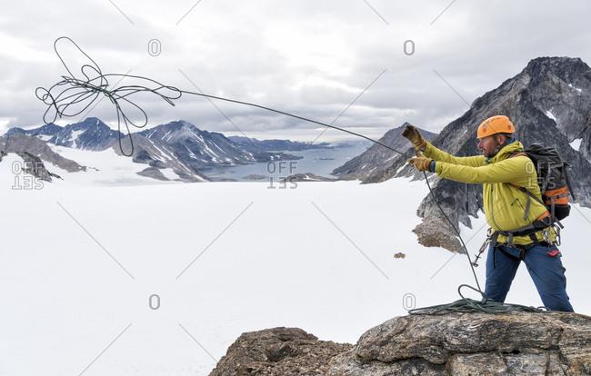 Greenland- Sermersooq- Kulusuk- Schweizerland Alps- mountaineer on summit throwing rope