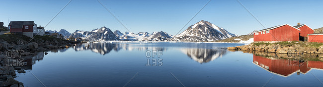 Greenland- Sermersooq- Kulusuk- Schweizerland Alps- mountains and wooden huts at the shore reflecting in water