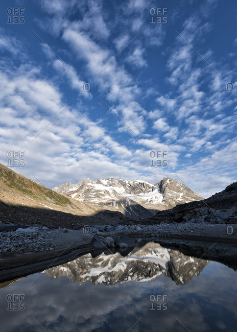 Greenland- Sermersooq- Kulusuk- Schweizerland Alps- man standing at lake with mountains reflecting in water