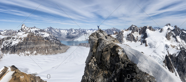 Greenland- Sermersooq- Kulusuk- Schweizerland Alps- mountaineer with raised arms on summit