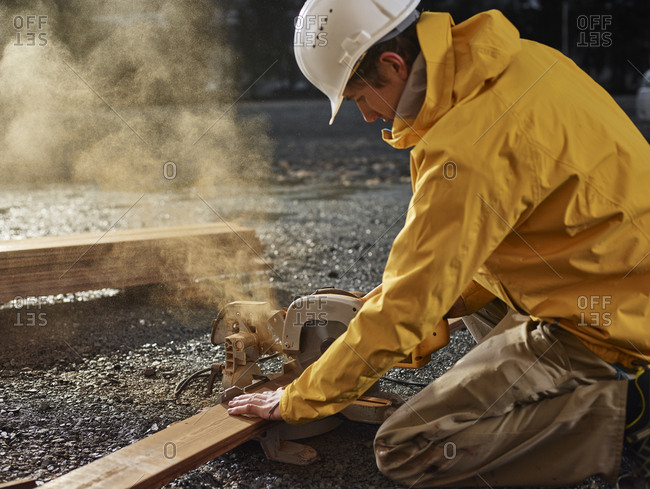 Man sawing decking board with circular saw