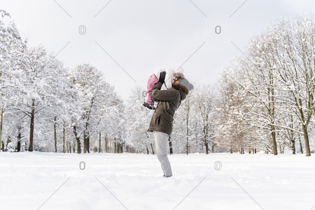 Happy affectionate father carrying daughter in winter landscape