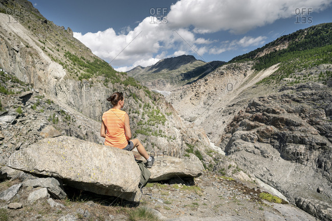 Switzerland- Valais- woman resting during a hiking trip in the mountains at Aletsch Glacier