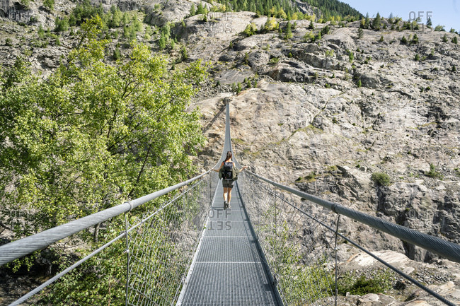 Switzerland- Valais- woman on a hiking trip in the mountains from Belalp to Riederalp on a swinging bridge