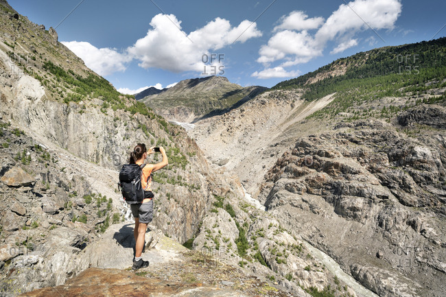 Switzerland- Valais- woman taking picture during a hiking trip in the mountains at Aletsch Glacier