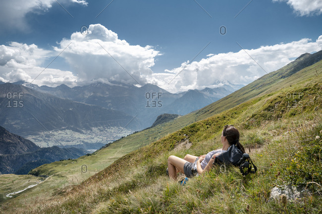 Switzerland- Valais- woman on a hiking trip in the mountains towards Foggenhorn lying on alpine meadow
