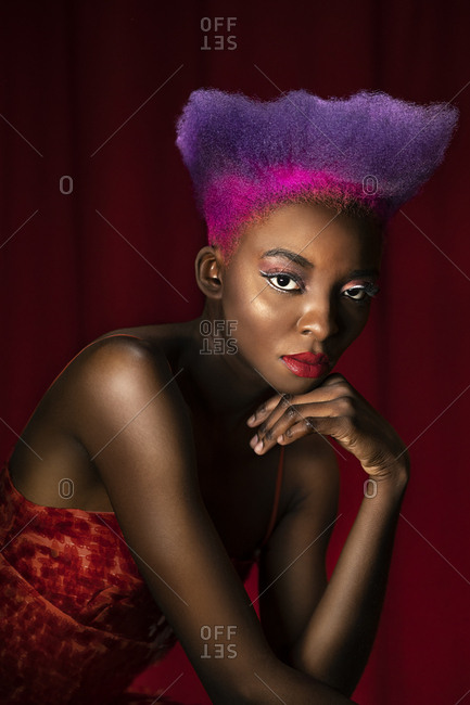 Portrait of lascivious young woman with pink and purple dyed hair
