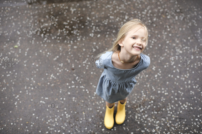 Girl wearing blue dress and rubber boots