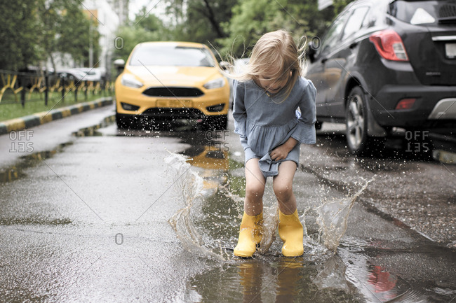 Girl wearing blue dress and rubber boots- jumping in pond on street- yellow car in the background