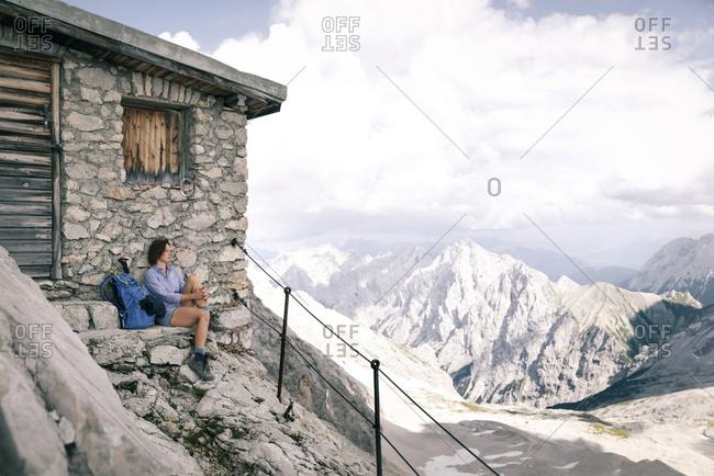 Austria- Tyrol- woman on a hiking trip resting at mountain hut