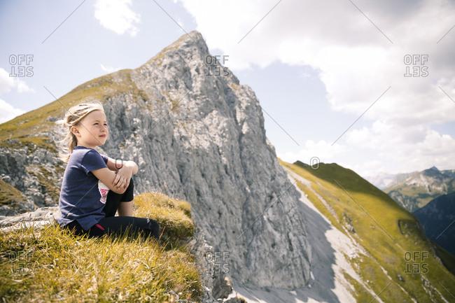 Austria- Tyrol- girl sitting in mountainscape