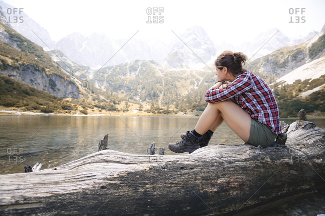 Austria- Tyrol- woman sitting on tree trunk at lake Seebensee