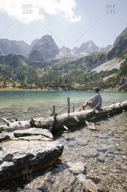 Austria- Tyrol- man sitting on tree trunk at lake Seebensee
