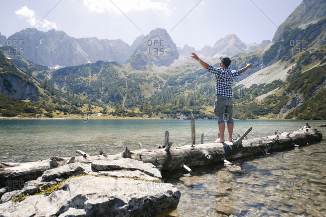 Austria- Tyrol- man standing on tree trunk at lake Seebensee