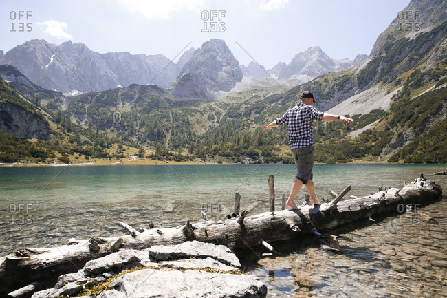 Austria- Tyrol- man balancing on tree trunk at lake Seebensee