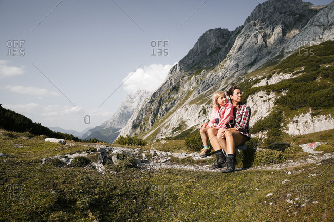 Austria- Tyrol- mother with daughter resting in mountainscape