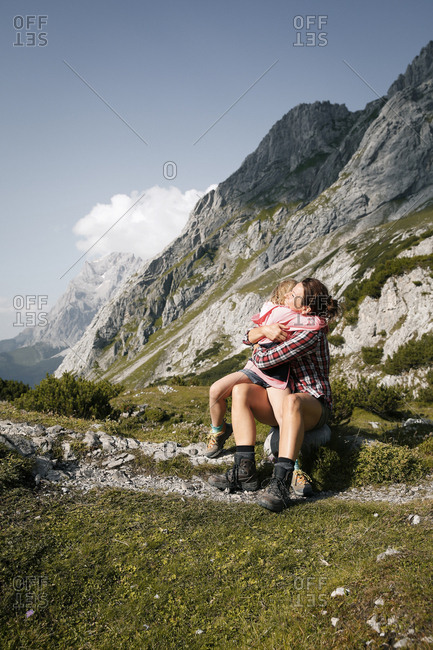Austria- Tyrol- happy mother and daughter hugging in mountainscape