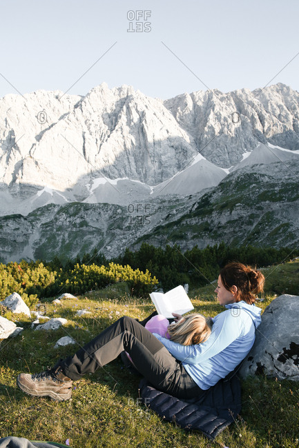 Austria- Tyrol- mother and daughter reading book in mountainscape