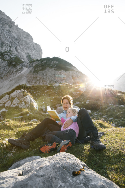 Austria- Tyrol- mother and daughter reading book in mountainscape at sunset