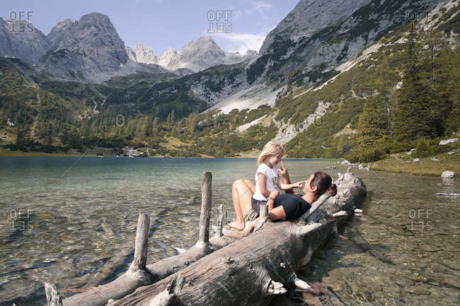 Austria- Tyrol- playful mother and daughter on tree trunk at lake Seebensee