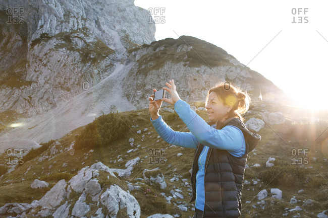 Austria- Tyrol- woman taking cell phone picture in mountainscape at sunset