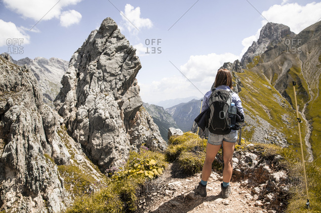 Austria- Tyrol- woman on a hiking trip in the mountains looking at view