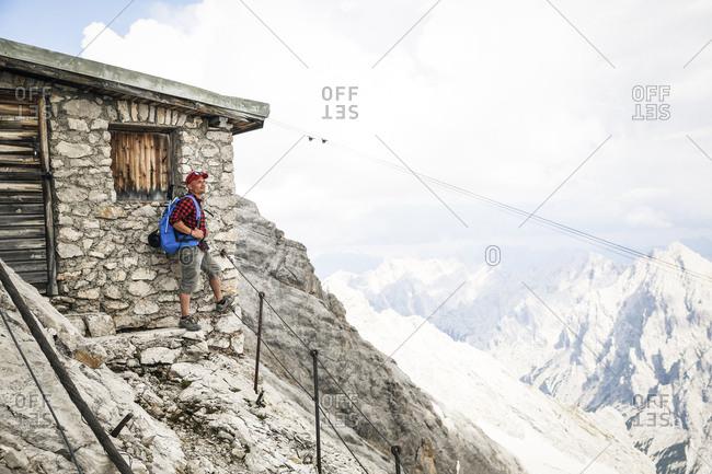 Austria- Tyrol- man on a hiking trip standing at mountain hut
