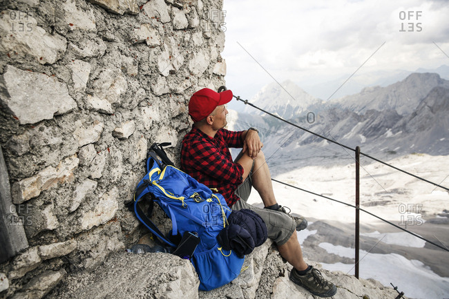 Austria- Tyrol- man on a hiking trip resting at mountain hut looking at view