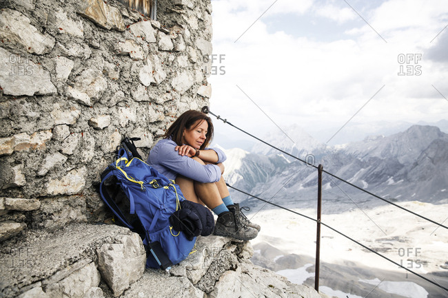 Austria- Tyrol- woman on a hiking trip resting at mountain hut with closed eyes