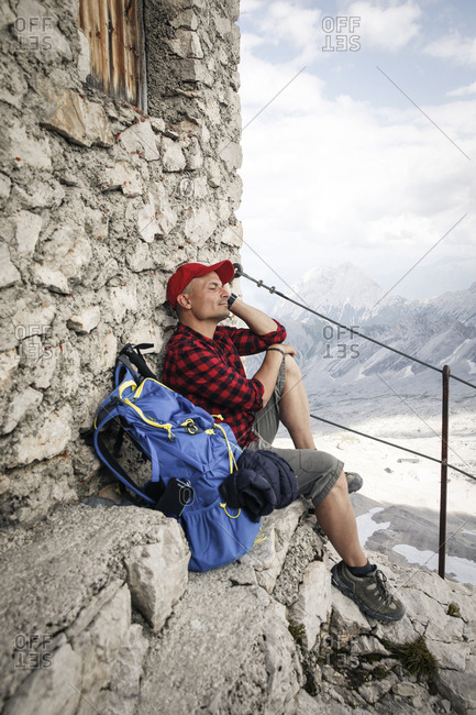 Austria- Tyrol- man on a hiking trip resting at mountain hut with closed eyes