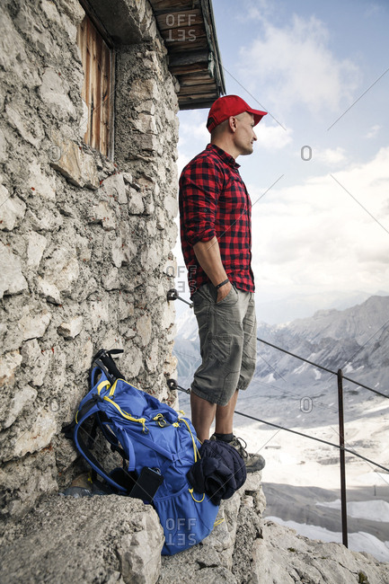 Austria- Tyrol- man on a hiking trip standing at mountain hut looking at view