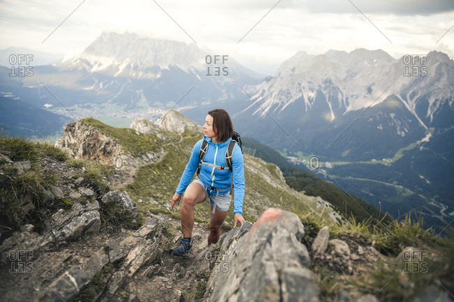Austria- Tyrol- woman on a hiking trip in the mountains looking around