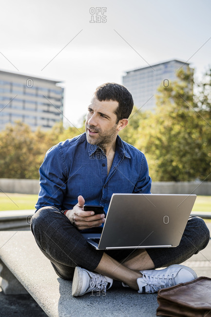 Businessman sitting on bench with smartphone and laptop looking at distance