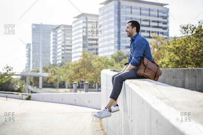 Relaxed man with leather bag sitting on wall