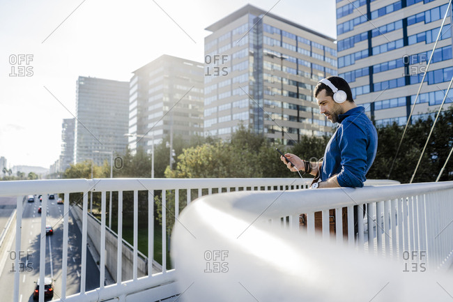 Man listening music with headphones and smartphones on a bridge